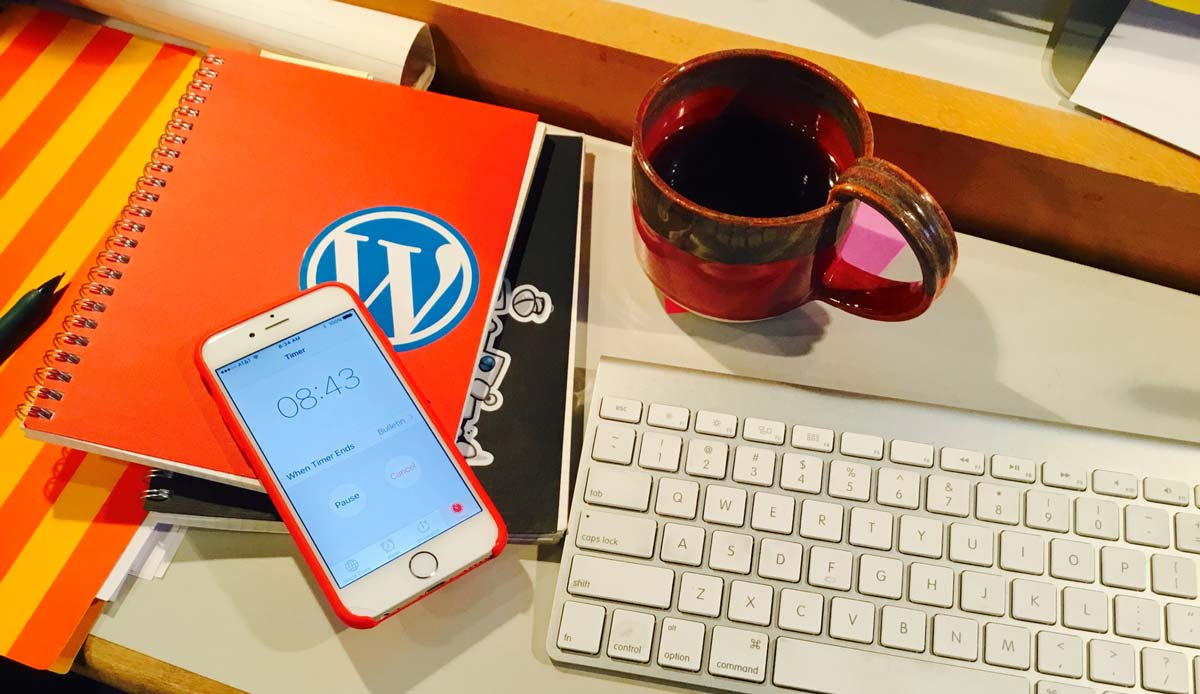 Desk with keyboard, coffee up and iPhone with the timer running reading 8 minutes