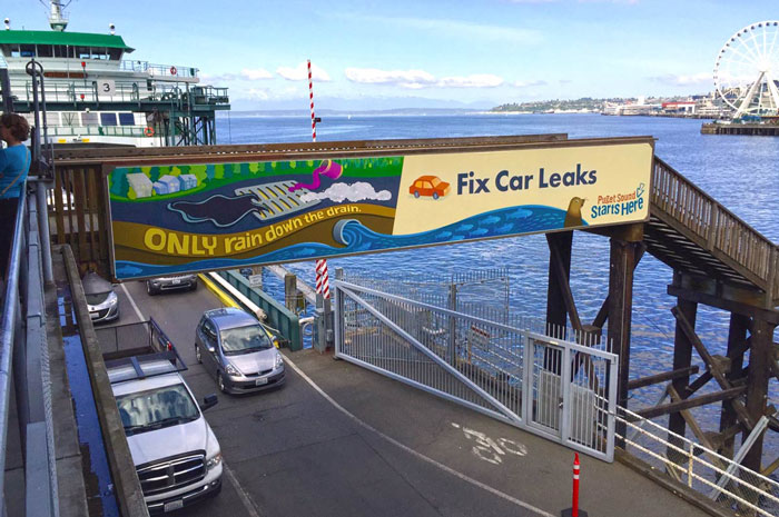 Only rain down the drain. Fix Car Leaks banner above the Colman Dock ferry terminal in Seattle